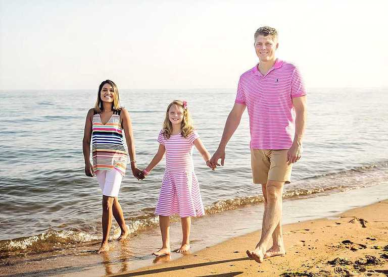mom and dad holding hands with daughter walking on the beach, connecticut family photographer