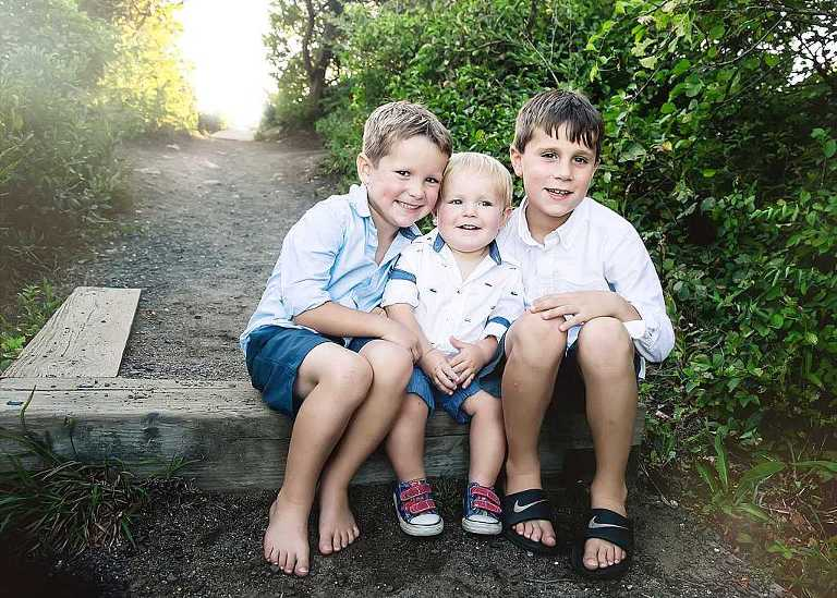 three brothers sitting on a step at the beach, westbrook family photography